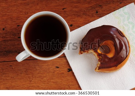 Overhead view of hot coffee with a doughnut with chocolate icing and a bite taken out of it