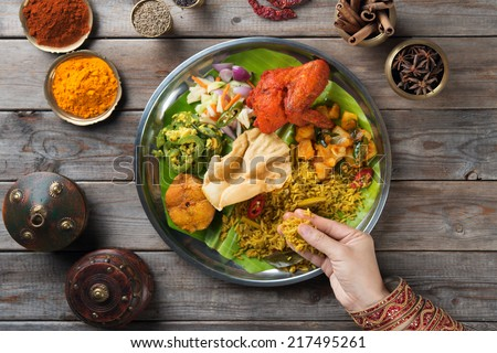 Overhead view of Indian woman's hand eating biryani rice on wooden dining table. - stock photo