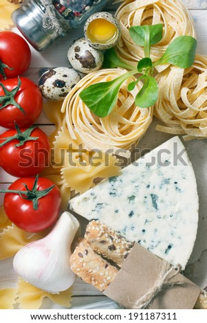 Overhead view of ingredients for an Italian pasta recipe on rustic wood background - stock photo