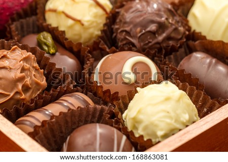 Overhead view of luxurious praline chocolates in open tray or box. - stock photo
