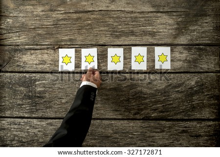 Overhead view of male hand placing five cards with golden stars on them in a row on a rustic wooden boards. Conceptual of service rating and quality of trade. - stock photo