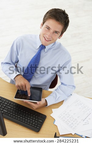 Overhead View Of Man Working At Desk Using Digital Tablet