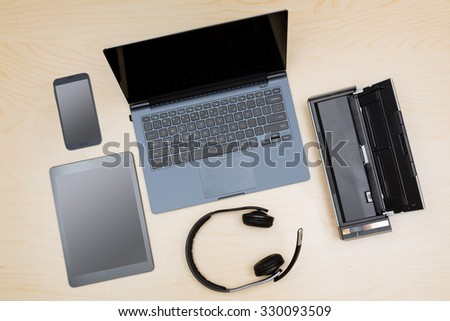 Overhead view of many computing and smartphone screens to illustrate the concept of teleworking or working from home
