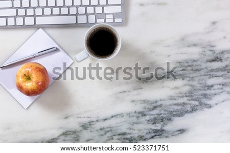 Overhead view of marble office desktop with computer keyboard, paper, pen, coffee, and apple.