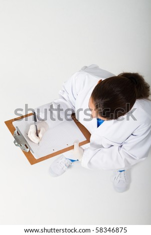 overhead view of medical nurse writing on clipboard
