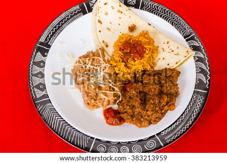 Overhead view of Mexican Dinner in high contrast black white and red setting.  Carne Guisada; refried beans; and Spanish Rice. - stock photo