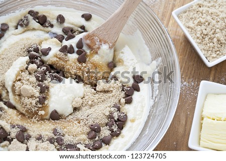 Overhead view of mixture of cookie preparation in bowl with spatula.