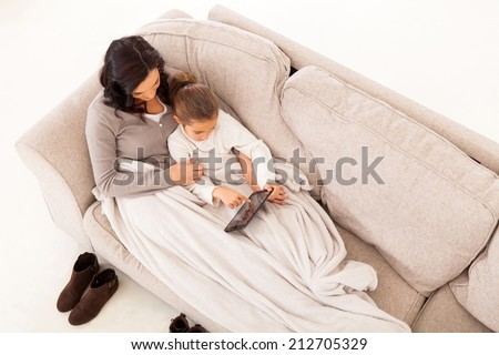 overhead view of mother and her daughter sitting on the couch using tablet computer - stock photo