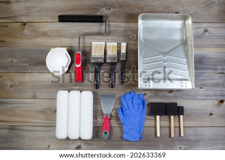 Overhead view of new painting accessories on rustic wood consisting of paint brushes, roller covers, pan, applicators, mask, latex gloves, scraper and hand roller frame - stock photo