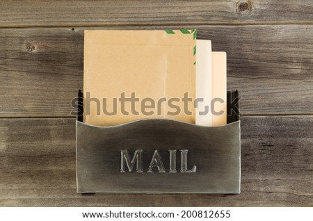 Overhead view of old metal mailbox with letters inside on rustic wooded boards - stock photo