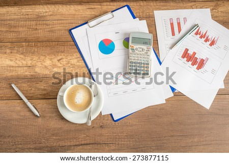 Overhead view of paperwork and graphs spread out with a calculator and cup of coffee on a wooden business desk. - stock photo