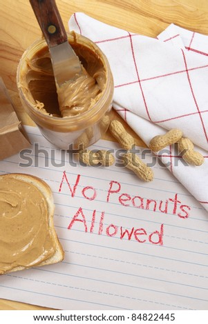 Overhead view of peanut butter on bread with red crayon warning against peanuts which are a dangerous allergen for many children and adults. - stock photo