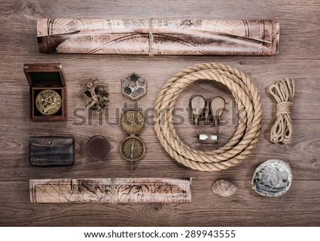 Overhead view of pirate or sailor gear laid out for a backpacking trip on a old wood floor. Items include, rope, compass, money, map, binoculars, hourglass, sextant , shell. Stories background. - stock photo