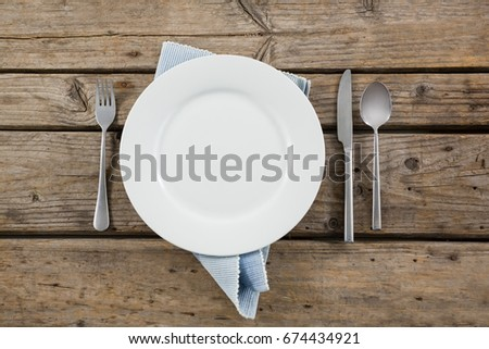 Overhead view of plate and cutlery with napkin on wooden table