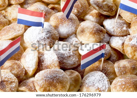 Overhead view of poffertjes with powdered soft sugar and dutch flags