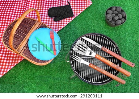 Overhead View Of Red Picnic Tablecloth, Plate, Fork, Knife, Barbecue Tools, Bucket With Charcoal Briquettes, BBQ Grill Appliance On The Summer Green Lawn Background - stock photo