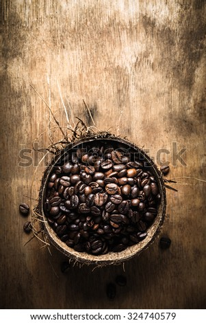 Overhead view of roasted coffee beans in coconut shell on rustic wooden background, Still life photography with roasted coffee beans - stock photo