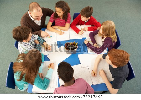 Overhead View Of Schoolchildren Working Together At Desk With Teacher - stock photo