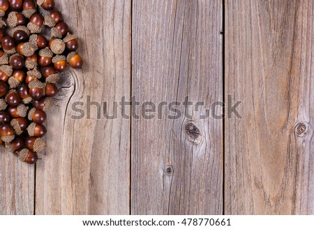Overhead view of seasonal autumn acorn decorations, upper left corner, on rustic wooden boards.