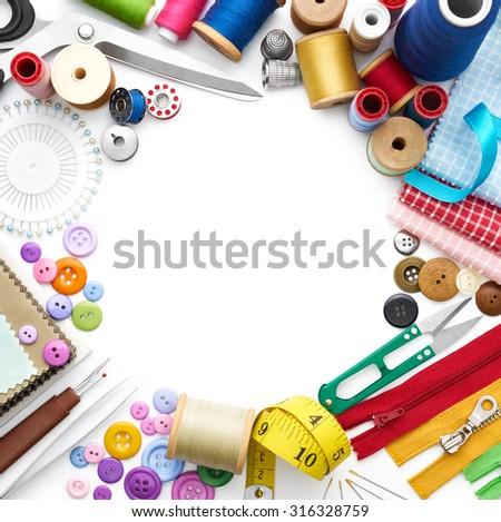 Overhead view of sewing tools and accessories on white background - stock photo