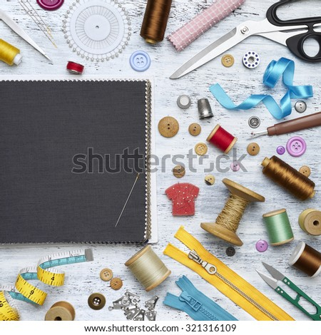 Overhead view of sewing tools and accessories on white painted wooden background - stock photo