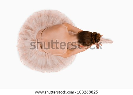 Overhead view of sitting ballerina against a white background - stock photo