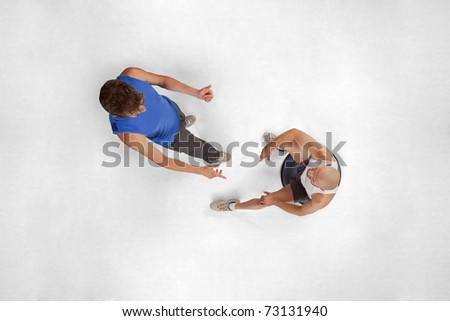 overhead view of sitting man listening to his personal trainer in gym - stock photo