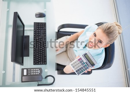 Overhead view of smiling businesswoman in bright office showing calculator - stock photo