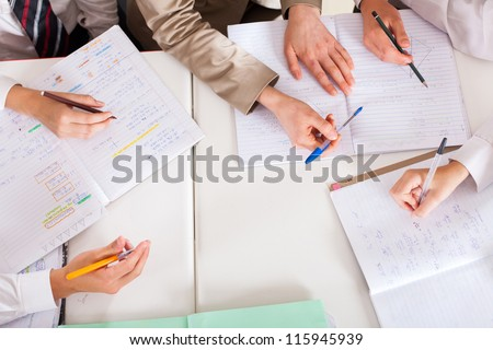 overhead view of teacher tutoring students in classroom - stock photo