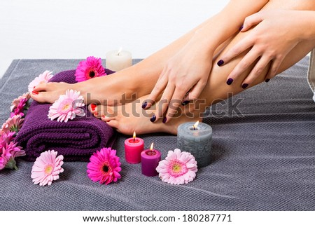Overhead view of the bare feet of a woman with beautiful manicured red nails resting on a purple towel surrounded by fresh colourful pink gerbera daisies in a spa or beauty salon - stock photo