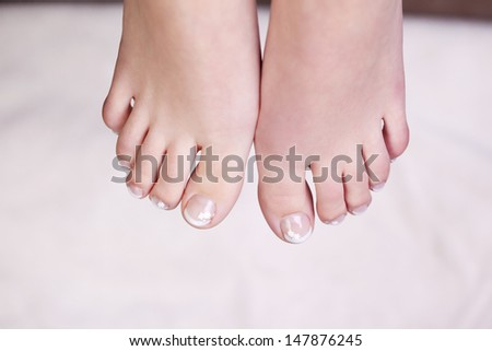 Overhead view of the bare feet of a woman with manicured toenails - stock photo