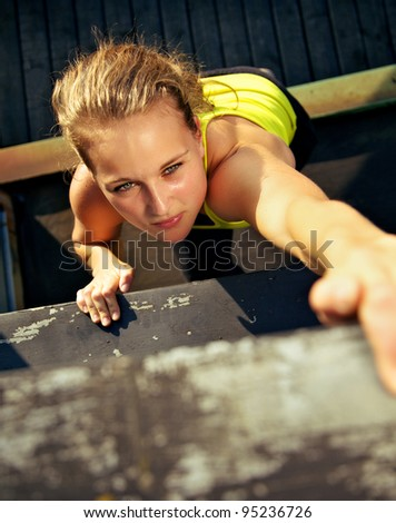 Overhead view of the concentration on the face of a woman traceur scaling the wall of an old industrial building during parkour - stock photo