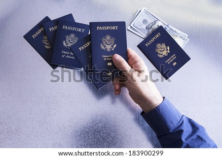 Overhead view of the hand of a man sorting and checking US passports with dollar bills tucked under one depicting a family man, customs official or tour guide with money for paying a fee or bribe - stock photo