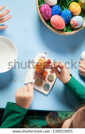 Overhead view of the hands of a child seated at a table painting colourful Easter eggs with a basket full of completed ones alongside