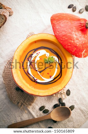 Overhead view of the hollowed out gourd filled with delicious orange autumn pumpkin soup drizzled with fresh cream - stock photo