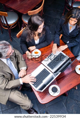 Overhead view of three business people meeting in a cafe - stock photo