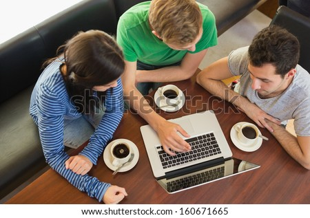 Overhead view of three students using laptop while having coffee at  the coffee shop - stock photo