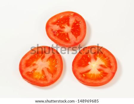 overhead view of three tomato slices - stock photo