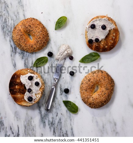 Overhead view of toasted bagels with cream cheese, blueberries, basil, and used knife on white marble stone.