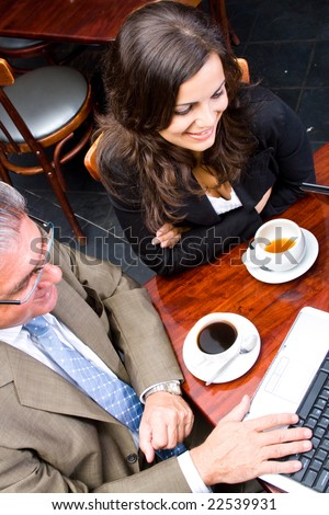 Overhead view of two business people meeting in a cafe - stock photo