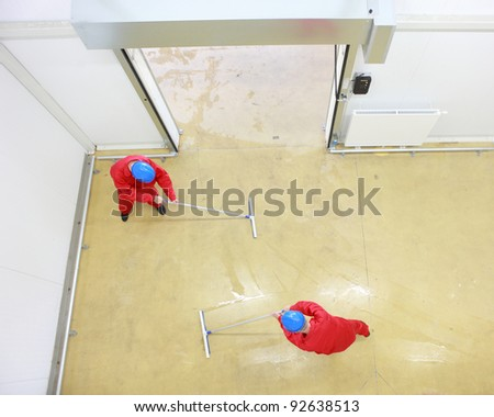 Overhead view of two workers in red uniforms and blue hardhats cleaning floor in industrial building - stock photo