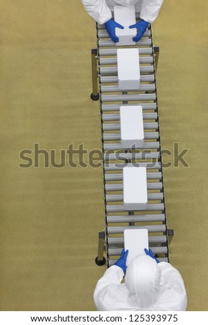 overhead view of two workers in white uniforms working with boxes on packing line - stock photo