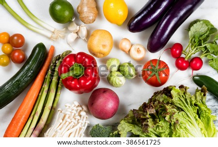 Overhead view of various whole vegetables and fruits, in fill frame format, on marble stone.