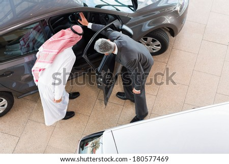 overhead view of vehicle salesman selling a car to arabian man - stock photo