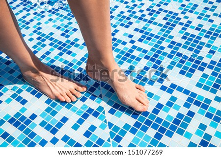 Overhead view of woman's legs in pool at luxury resort - stock photo