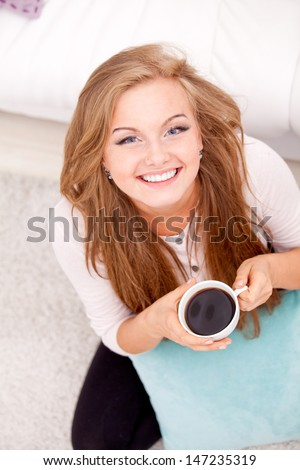Overhead view of woman sitting on floor with some coffee and pillow at home