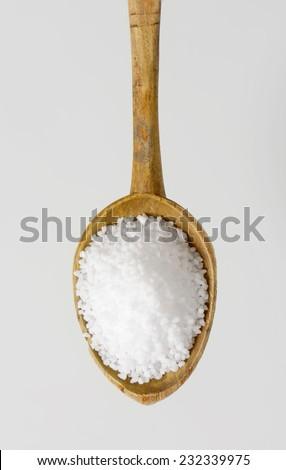overhead view of wooden teaspoon with sea salt - stock photo