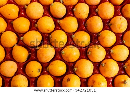 Overhead view of yellow Loquat fruit nested in a red plastic tray for shipping and display showing a repetitive pattern. - stock photo