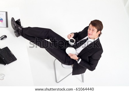 overhead view of young businessman drinking coffee in office - stock photo