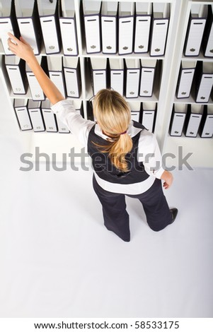 overhead view of young happy businesswoman searching file in office - stock photo